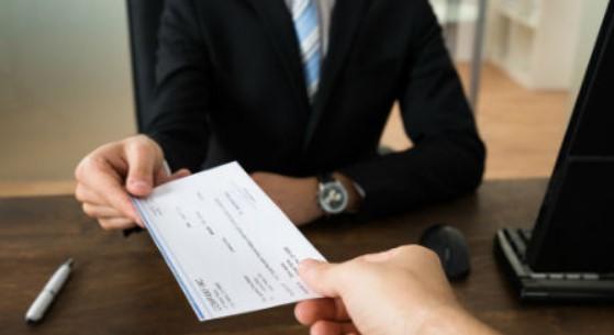 Empresario entregando la liquidación en forma de cheque a un trabajador al que ha despedido.